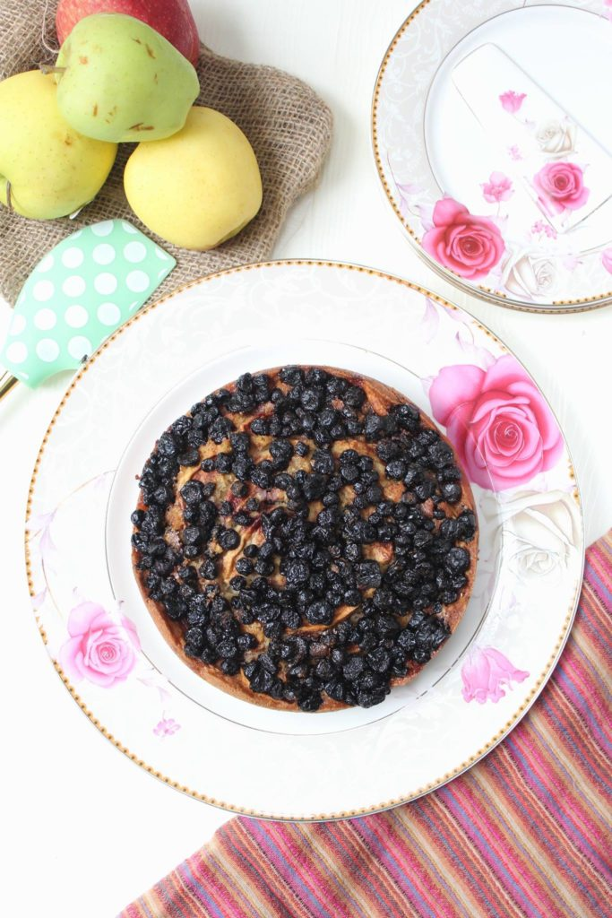 Cake topped with Apple wedges and frozen blackberries