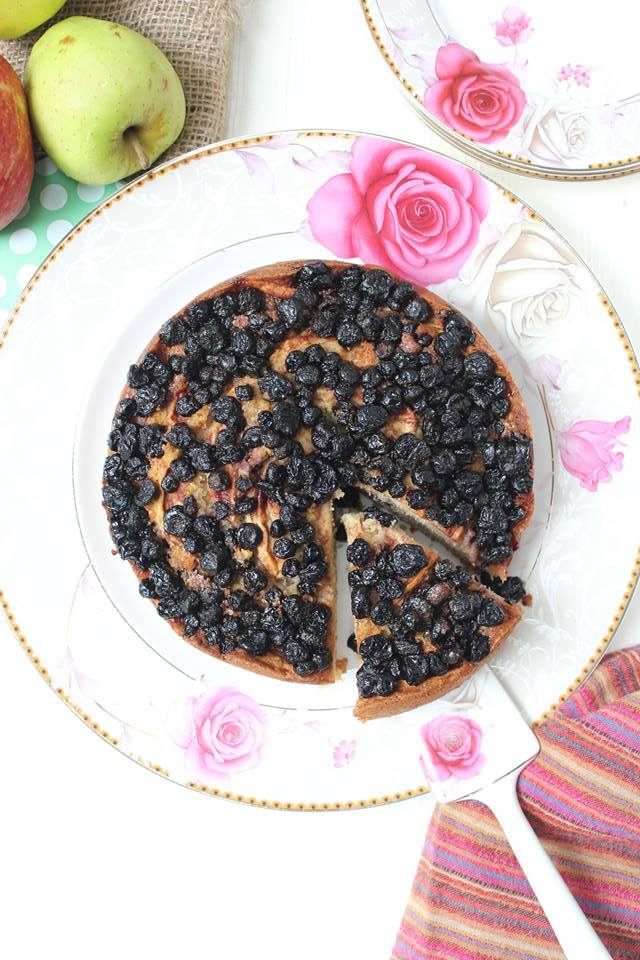 Fall cake topped with apple wedges and blackberries